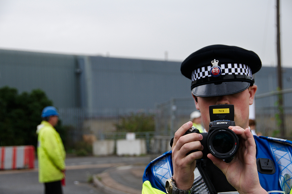 FIT (Forward Intelligence Team) officer films me while activists from the Climate Camp at Kingsnorth block the access road to the Vopak fuel storage depot and hang a banner from one of the tanks in Purfleet, Essex, in a protest at increasing carbon emissions.  7 August 2008.